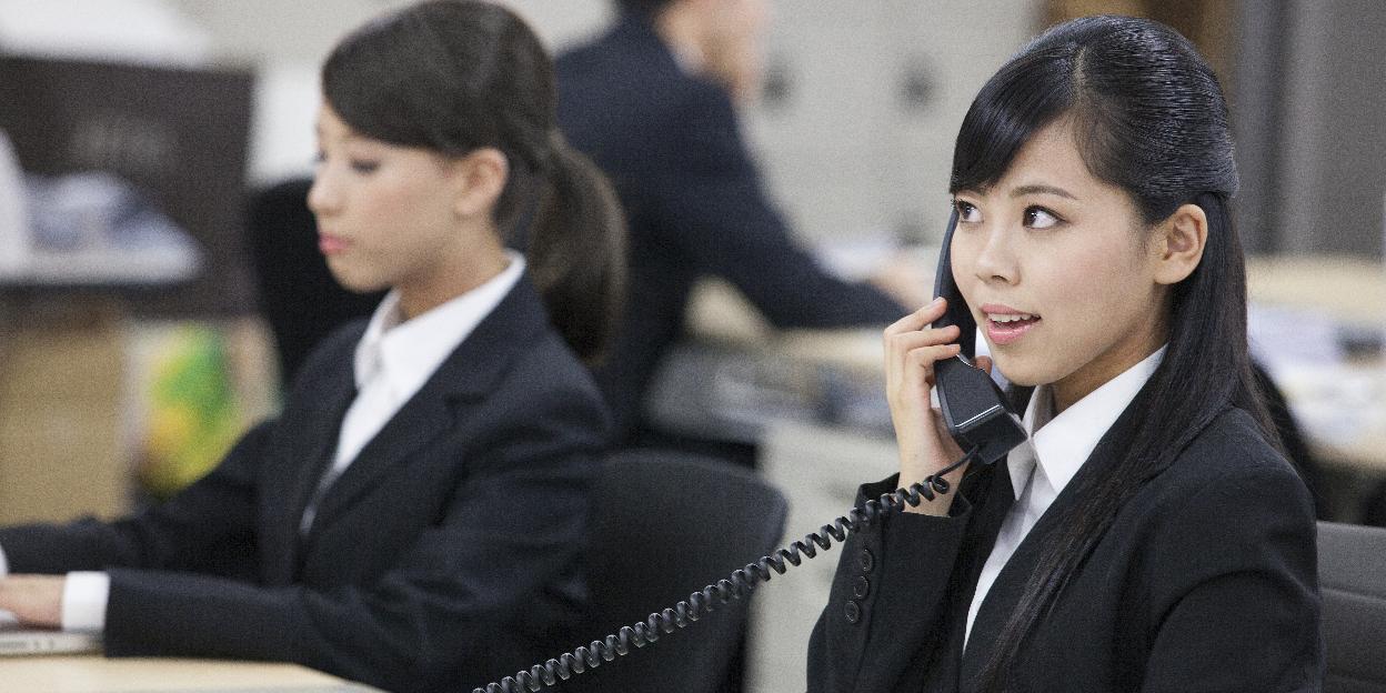 ヘルプデスクで電話応対する女性
